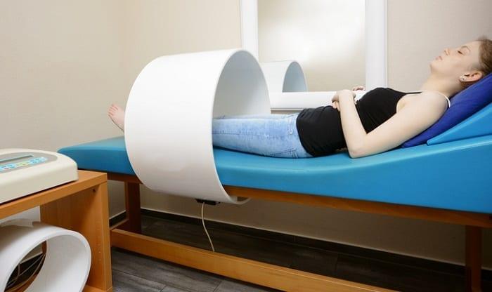 Frau führt pulsierende Magnetfeldtherapie durch
