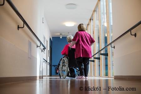Frau schiebt eine Pflegebedürftige Seniorin durch einen Flur