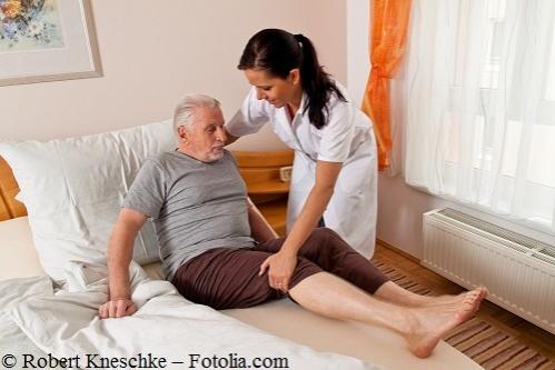 Pflegerin hilft Pflegebedürftigen Mann aus dem Bett