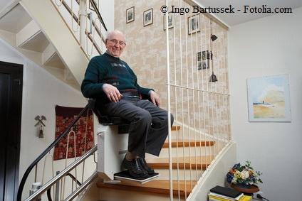 Pflegebedürftiger Senior fährt mit dem Treppenlift nach oben