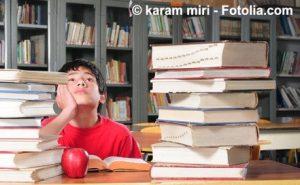 Junge verzweifelt vor Büchern