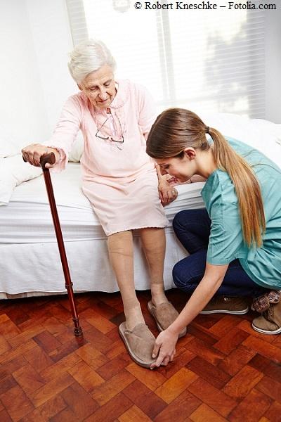 Pflegerin hilft einer Pflegebedürftigen Seniorin in die Hausschuhe