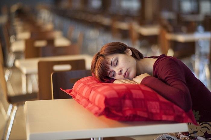 Frau schläft im Sitzen, mit einem Kissen auf dem Tisch