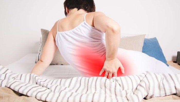 Frau halb sitzend auf Ihrer Matratze mit Rückenschmerzen