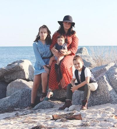 Frau am Strand mit 3 Kindern