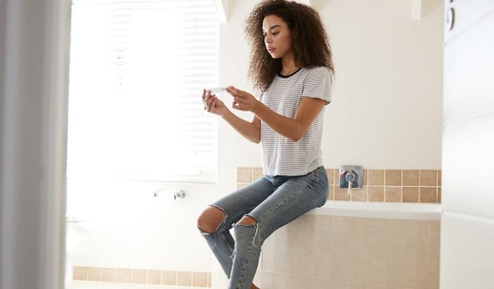 Junge Frau beim Schwangerschaftstest