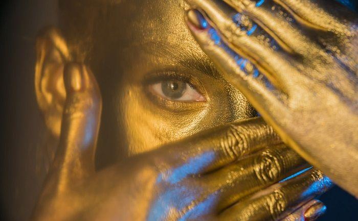 Goldfarben geschminkte Frau verdeckt Ihr Gesicht