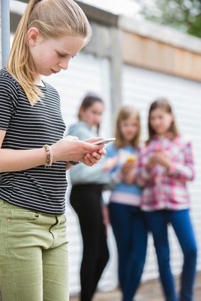 Kind mit Handy, Freundinnen im Hintergrund