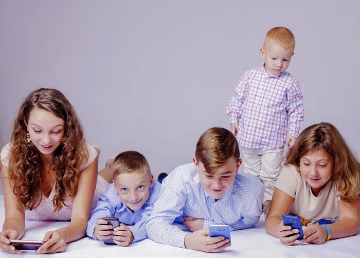 Kinder in jeder Altersgruppe spielen mit ihren Handys