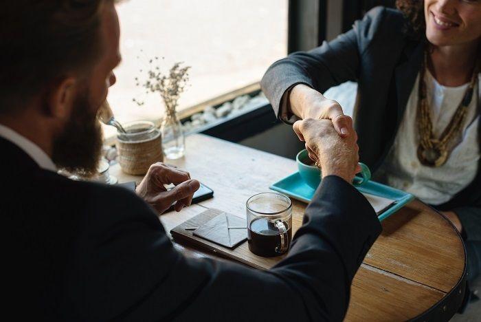 Mann und Frau am Tisch, geben sich die Hand
