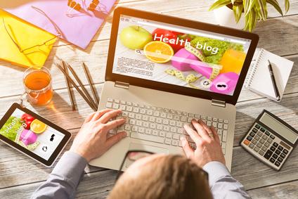 Mann sitzt vor seinem Laptop und Blogt einen Artikel