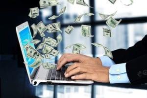 Mann mit Laptop und Geldregen