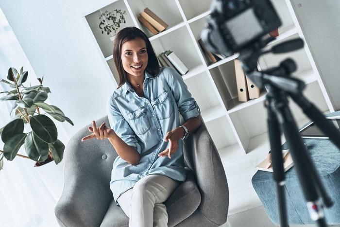 Frau sitzt vor der Kamera und erklärt etwas