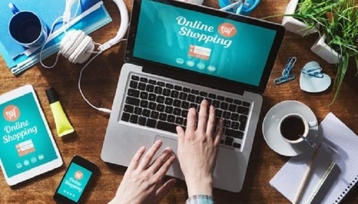 Mann tippt am Laptop in einem Online Shopping Portal