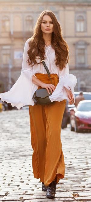 Frau mit weit geschnittener Hose geht über die Strasse