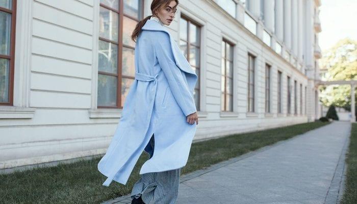 Frau mit weitem blauen Mantel geht am Gehweg