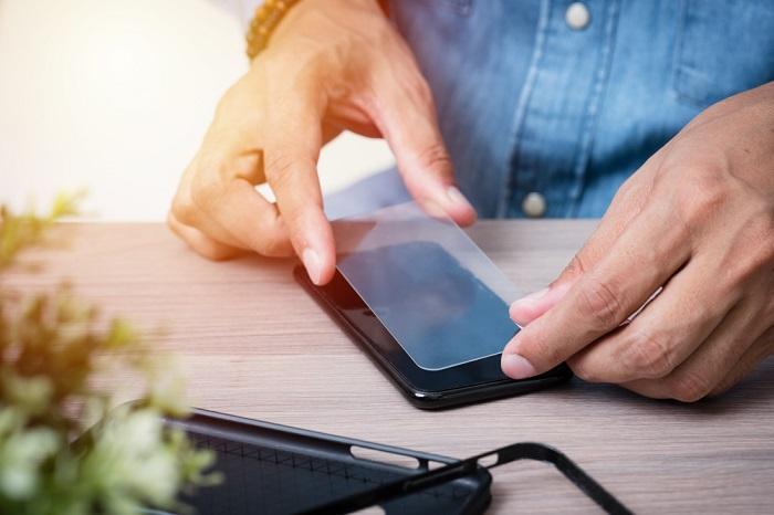 Mann bringt Displayschutz aufs Smartphone