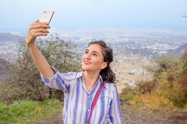 Frau steht auf einem Berg und macht ein Selfie von sich