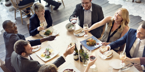 Menschen sitzen an einem Tisch und feiern