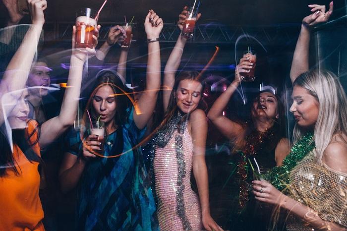 Frauen tanzen mit Cocktails auf einer Party
