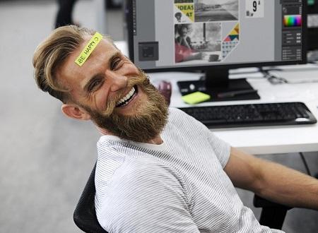 Lachender Mann mit Be Happy Aufkleber auf der Stirn