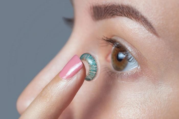 Frau verucht eine Kontaktlinse einzusetzen
