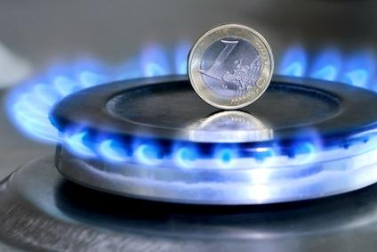 Ein ein Eurostück steht auf einem Herd mit Gasflamme