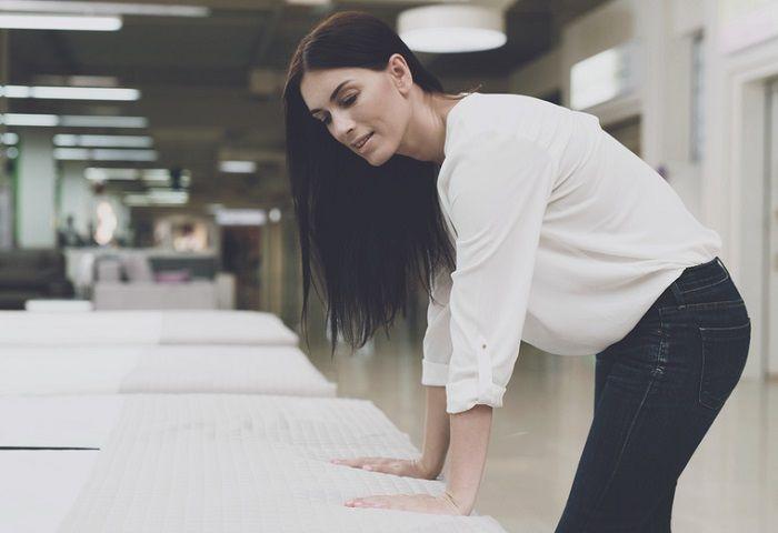 Frau testet in einem Geschäft eine Matratze