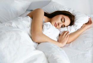 Frau liegt in Seitenlage im Bett
