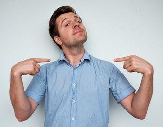 Mann steht angeberisch da und deutet mit beiden Zeigefingern auf sich selbst
