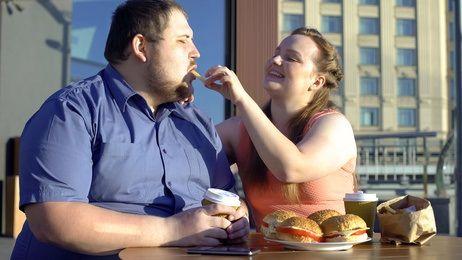 Eine dicke Frau füttert einen noch dickeren Mann mit Pommes und Burgern