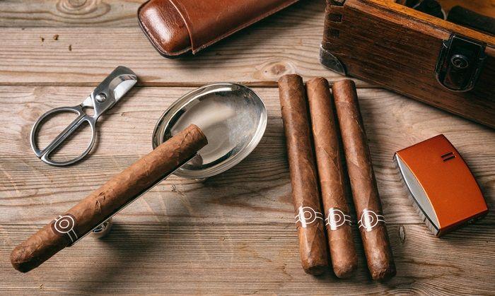 Eine Zigarre mit edlen Utensilien liegt auf einem Holztisch