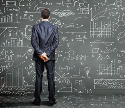 Mann steht vor einer großen Tafel mit vielen Formeln und Diagrammen