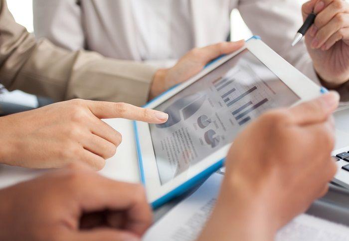 Frau zeigt mit Finger auf ein Tablet auf dem sich Statistiken befinden