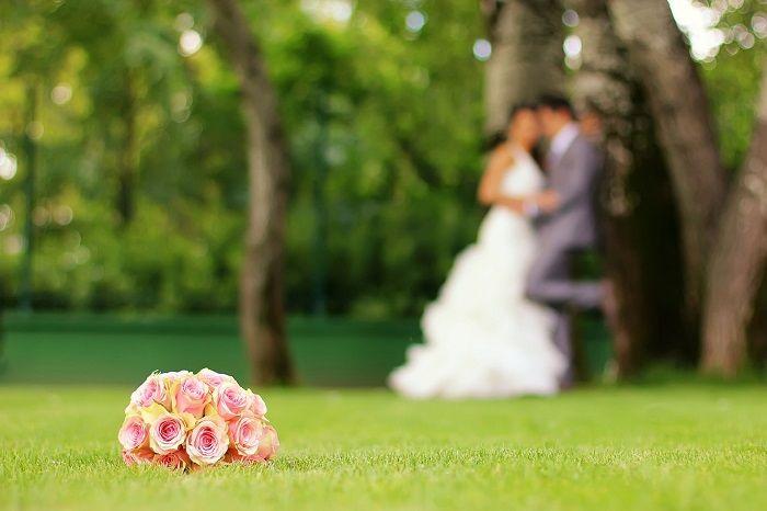 Brautstrauß liegt auf der Wiese und Brautpaar lehnt an einem Baum