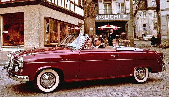 Ein weinrotes Borgward Cabriolet fährt über einen alten Stadtplatz
