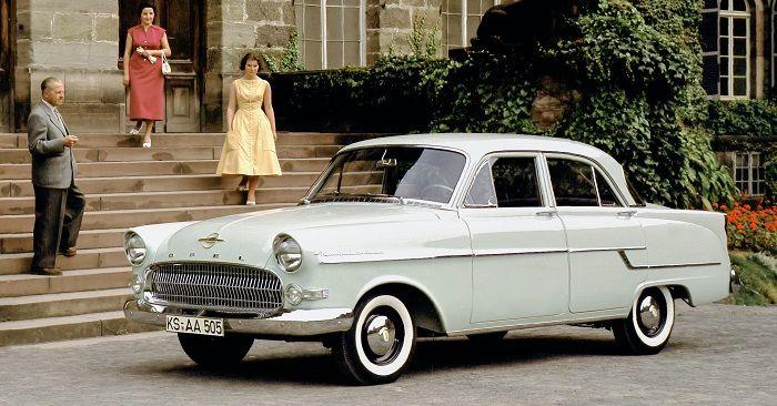 Ein lindgrüner Opel Kapitän Baujahr 1955 steht vor einem Herrschaftshaus