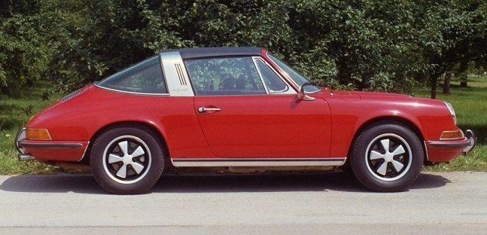 Ein roter Porsche Targa Baujahr 1972 vor einer Hecke