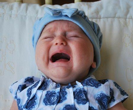 Baby liegt weinend im Bett