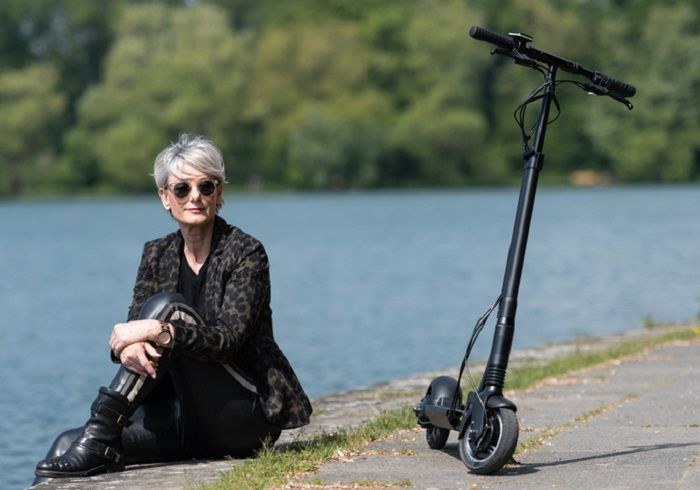 Frau sitzt am Wasser, neben ihr steht ein E-Scooter