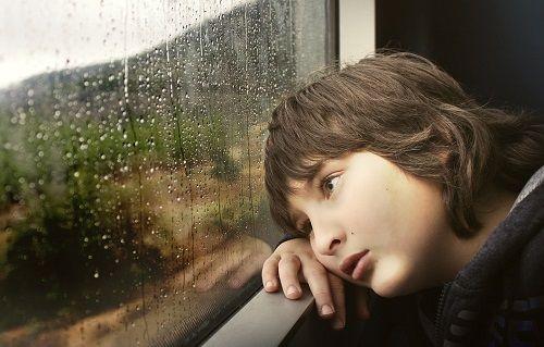 Junge sitzt traurig an einem Zugfenster