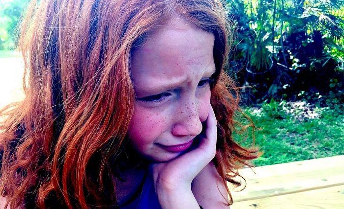 Mädchen sitzt traurig und weinend am Tisch