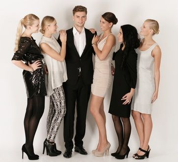Junger Mann steht in der Mitte, flankiert von fünf Frauen die Ihn Bewundern
