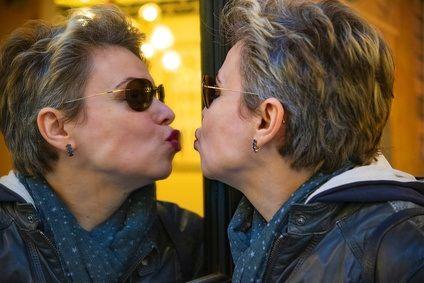 Frau küsst sich im Spiegel