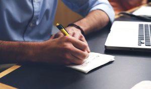 Mann macht schreibt Notizen auf einen Zettel