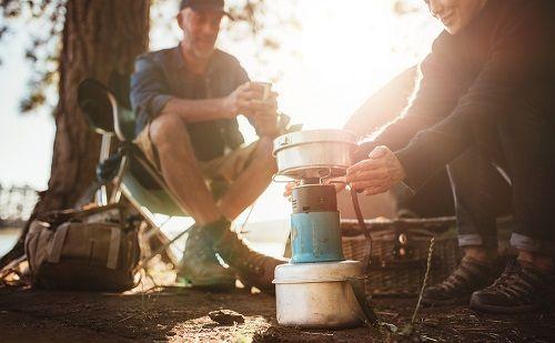 Ein Paar kocht in freier Natur mit dem Gaskocher