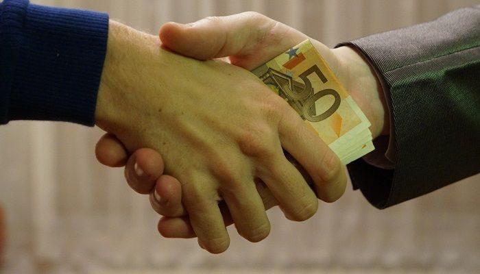 Mann gibt per Handschlag jemandem Geld