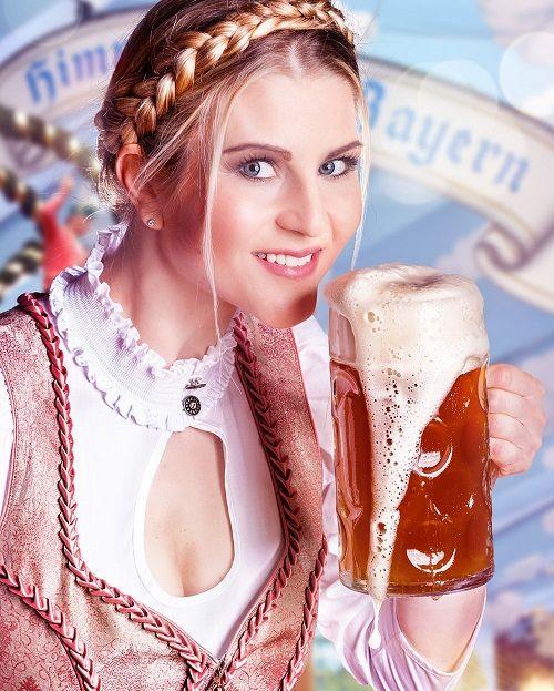 Frau im Dirndl hebt eine Mass Bier zum trinken an