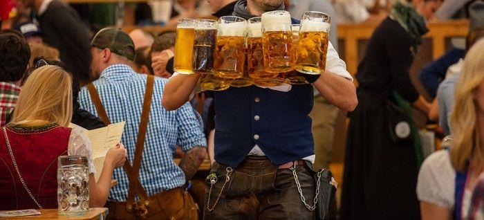 Ein Ober trägt 11 Mass Bier im Zelt