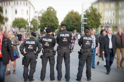 Polizisten stehen vor Passanten die zur Wiesn wollen